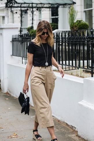 Cómo combinar: camiseta con cuello circular negra, falda pantalón en beige, sandalias con cuña de cuero negras, cartera sobre de cuero negra