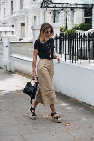Cómo combinar: camiseta con cuello circular negra, falda pantalón marrón claro, sandalias con cuña de cuero negras, cartera sobre de cuero negra