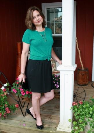 Cómo combinar: camiseta con cuello circular verde, falda skater negra, bailarinas de cuero negras, cartera sobre de ante negra