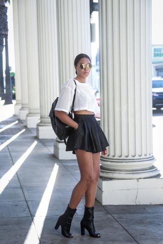 Cómo combinar: camiseta con cuello circular de malla blanca, falda skater de cuero negra, botines de cuero con recorte negros, mochila de cuero negra