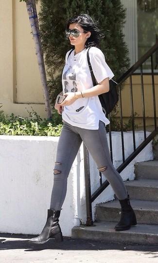 Cómo combinar: camiseta con cuello circular estampada blanca, leggings vaqueros grises, botas a media pierna de cuero negras, mochila de cuero negra