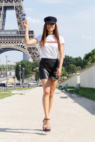 Cómo combinar: camiseta con cuello circular estampada en blanco y rojo, minifalda de cuero negra, sandalias de tacón de cuero en marrón oscuro, gorra inglesa negra