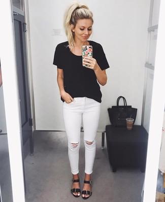 Cómo combinar: camiseta con cuello circular negra, vaqueros pitillo desgastados blancos, sandalias planas de cuero negras