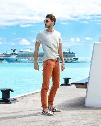 Cómo combinar: camiseta con cuello circular blanca, pantalón chino naranja, alpargatas de lona de rayas horizontales blancas, correa de lona tejida blanca