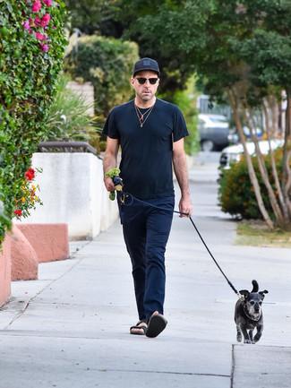 Cómo combinar: camiseta con cuello circular negra, pantalón chino azul marino, sandalias de cuero negras, gorra de béisbol negra