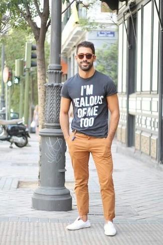 Cómo combinar: camiseta con cuello circular estampada en gris oscuro, pantalón chino marrón claro, tenis de lona blancos, gafas de sol marrónes