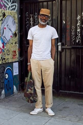 Cómo combinar: camiseta con cuello circular gris, pantalón chino en beige, tenis blancos, bolsa tote de lona de camuflaje verde oscuro