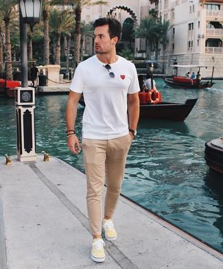 Cómo combinar: camiseta con cuello circular blanca, pantalón chino marrón claro, tenis de lona amarillos, gafas de sol negras