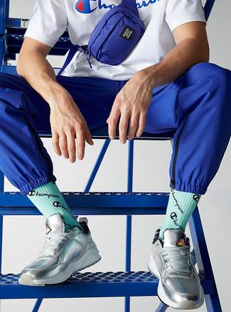 Cómo combinar: camiseta con cuello circular estampada en blanco y azul, pantalón de chándal azul, tenis de cuero plateados, riñonera de lona azul