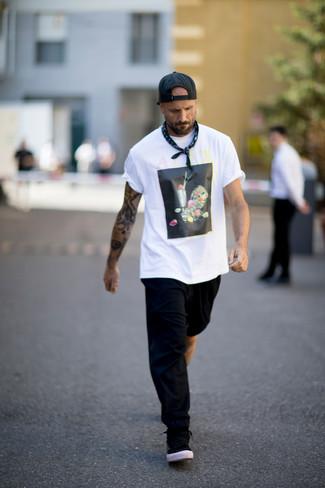 Cómo combinar: camiseta con cuello circular estampada en blanco y negro, pantalón de chándal negro, tenis negros, gorra de béisbol negra