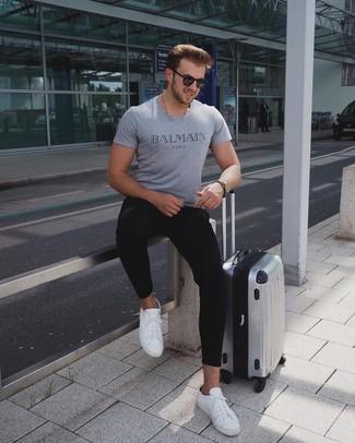 Cómo combinar: camiseta con cuello circular estampada gris, pantalón de chándal negro, tenis de cuero blancos, maleta plateada