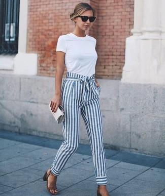 Cómo combinar: camiseta con cuello circular blanca, pantalón de pinzas de rayas verticales en blanco y azul, sandalias de tacón de cuero marrónes, cartera sobre de cuero gris
