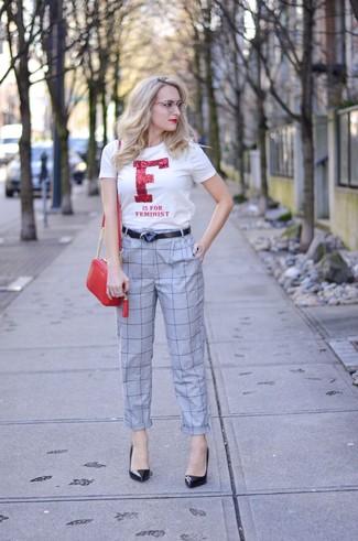 Cómo combinar: camiseta con cuello circular estampada en blanco y rojo, pantalón de pinzas a cuadros gris, zapatos de tacón de cuero negros, bolso bandolera de cuero rojo