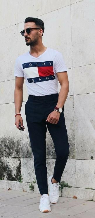 Cómo combinar: camiseta con cuello circular estampada blanca, pantalón de vestir negro, tenis de cuero blancos, gafas de sol negras