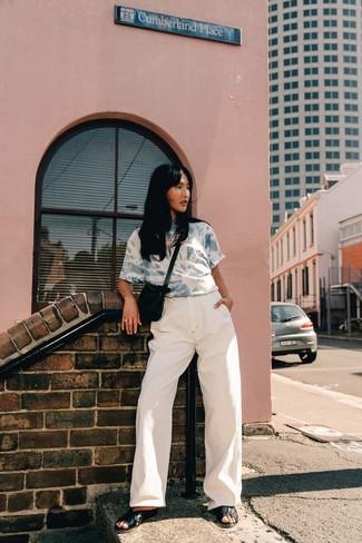 Cómo combinar: camiseta con cuello circular con lavado ácido celeste, pantalones anchos vaqueros blancos, sandalias planas de cuero negras, bolso bandolera de ante negro