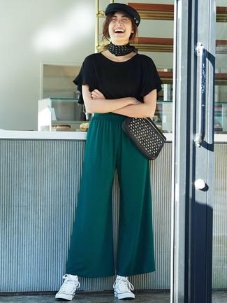 Cómo combinar: camiseta con cuello circular con volante negra, pantalones anchos verde oscuro, zapatillas altas de lona blancas, cartera sobre de cuero con tachuelas negra
