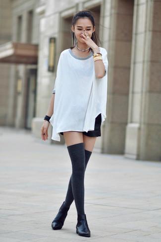 Cómo combinar: camiseta con cuello circular de seda blanca, pantalones cortos de cuero negros, botines chelsea de cuero negros, calcetines hasta la rodilla en gris oscuro