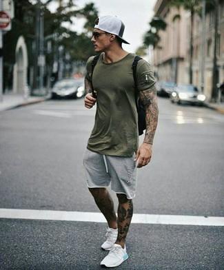 Cómo combinar: camiseta con cuello circular verde oliva, pantalones cortos grises, deportivas blancas, mochila de lona negra