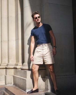 Cómo combinar: camiseta con cuello circular azul marino, pantalones cortos en beige, mocasín de cuero en marrón oscuro, gafas de sol verde oliva