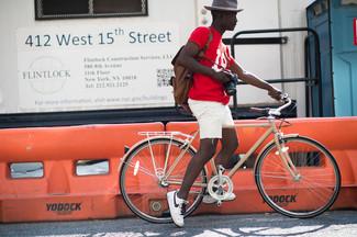 Cómo combinar: camiseta con cuello circular estampada en rojo y blanco, pantalones cortos vaqueros blancos, tenis en blanco y negro, mochila de cuero en marrón oscuro