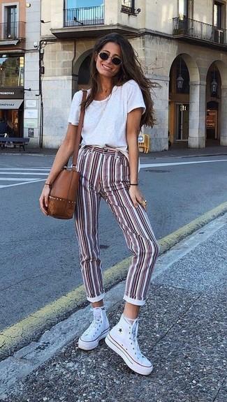 Cómo combinar: camiseta con cuello circular blanca, pantalones pitillo de rayas verticales en blanco y rojo, zapatillas altas de lona blancas, bolso bandolera de cuero marrón