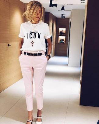 Cómo combinar: camiseta con cuello circular estampada en blanco y negro, pantalones pitillo rosados, zapatos de tacón de cuero blancos, correa de cuero negra