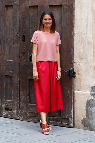 Cómo combinar: camiseta con cuello circular rosada, falda pantalón roja, sandalias de tacón de cuero marrónes