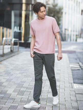 Cómo combinar: camiseta con cuello circular rosada, pantalón chino en gris oscuro, tenis de cuero blancos