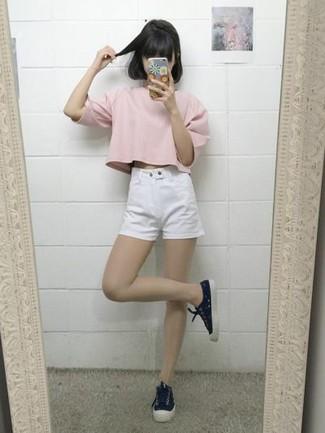 Cómo combinar: camiseta con cuello circular rosada, pantalones cortos vaqueros blancos, tenis de lona negros