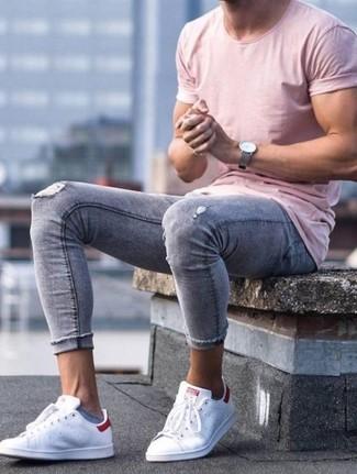 Cómo combinar: camiseta con cuello circular rosada, vaqueros pitillo desgastados grises, tenis de cuero blancos, reloj de cuero gris