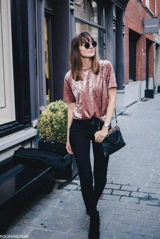 Cómo combinar: camiseta con cuello circular de terciopelo rosada, vaqueros pitillo negros, botines chelsea de ante negros, bolso bandolera de cuero negro