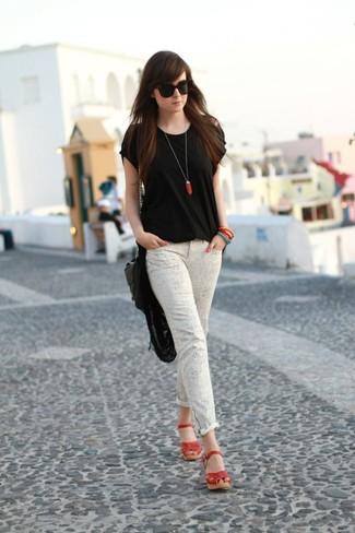 Cómo combinar: camiseta con cuello circular negra, vaqueros pitillo grises, sandalias con cuña de cuero rojas, bolso bandolera de cuero negro