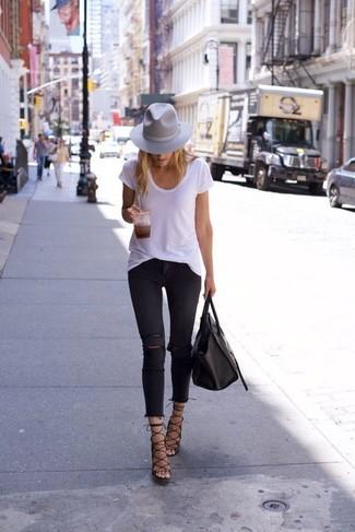 Cómo combinar: camiseta con cuello circular blanca, vaqueros pitillo desgastados negros, sandalias de tacón de cuero negras, bolsa tote de cuero negra