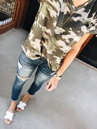 Cómo combinar: camiseta con cuello circular de camuflaje verde oliva, vaqueros pitillo desgastados azul marino, sandalias planas de cuero blancas, colgante dorado