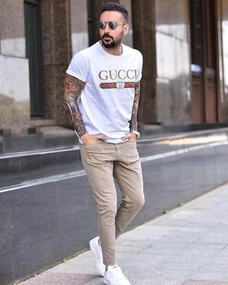 Cómo combinar: camiseta con cuello circular estampada blanca, vaqueros pitillo en beige, tenis de cuero blancos, gafas de sol grises
