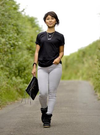 Para seguir las tendencias usa una camiseta con cuello circular negra y unos vaqueros pitillo grises. Complementa tu atuendo con zapatillas con cuña de ante negras.