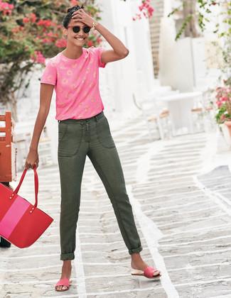 Cómo combinar: camiseta con cuello circular estampada rosa, vaqueros verde oliva, sandalias planas de ante rosa, bolsa tote de cuero roja