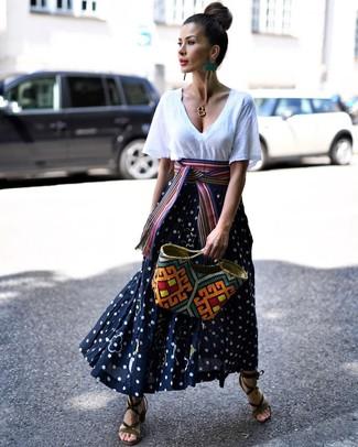 Cómo combinar: camiseta con cuello en v blanca, falda larga a lunares en azul marino y blanco, sandalias de tacón de ante verde oliva, bolsa tote de paja en multicolor