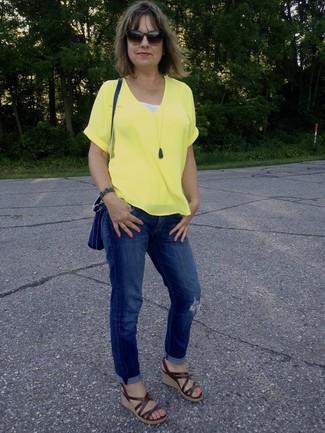 Cómo combinar: camiseta con cuello en v amarilla, vaqueros boyfriend desgastados azules, sandalias con cuña de cuero marrónes, bolso bandolera de cuero azul