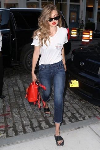 Cómo combinar: camiseta con cuello en v estampada blanca, vaqueros pitillo azul marino, sandalias planas de cuero negras, mochila de cuero roja