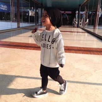 Cómo combinar: camiseta de manga larga de rayas verticales blanca, pantalón de chándal negro, zapatillas en negro y blanco, gorro negro