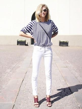 Cómo combinar: camiseta de manga larga de rayas horizontales en blanco y azul marino, vaqueros blancos, sandalias de tacón de cuero burdeos, bolso bandolera de cuero negro