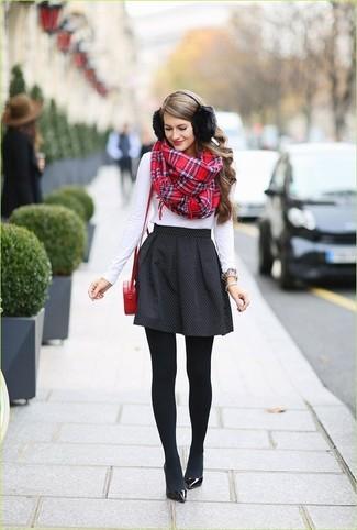 Cómo combinar: camiseta de manga larga blanca, falda skater a lunares negra, zapatos de tacón de cuero negros, bolso bandolera de cuero rojo