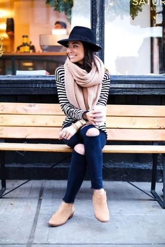 Look de moda: Camiseta de manga larga de rayas horizontales en blanco y negro, Vaqueros pitillo desgastados azul marino, Botines de ante marrón claro, Sombrero de lana negro