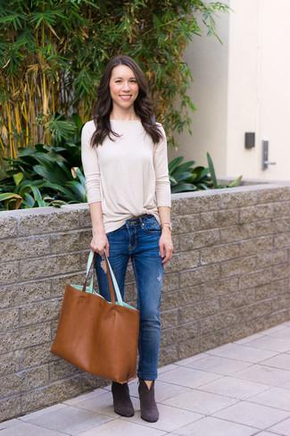 Cómo combinar: camiseta de manga larga en beige, vaqueros pitillo desgastados azules, botines de ante en gris oscuro, bolsa tote de cuero en tabaco