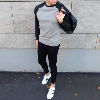 Cómo combinar: camiseta de manga larga gris, vaqueros pitillo negros, tenis en blanco y negro, bolsa tote de cuero negra
