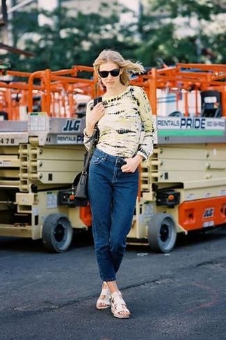 Cómo combinar: camiseta de manga larga efecto teñido anudado amarilla, vaqueros azul marino, sandalias planas de cuero blancas, bolso bandolera de cuero negro