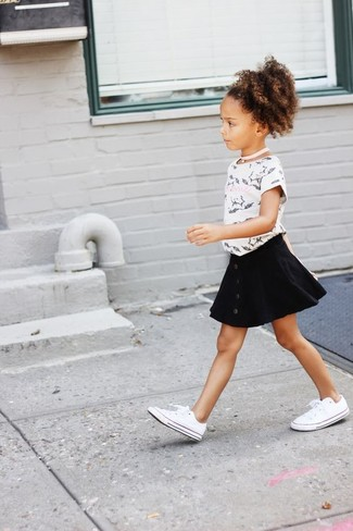 Cómo combinar: camiseta estampada en blanco y negro, falda negra, zapatillas blancas