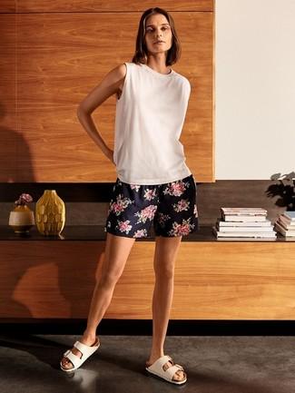 Cómo combinar: camiseta sin manga blanca, pantalones cortos con print de flores azul marino, sandalias planas de cuero blancas