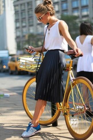 Los días ocupados exigen un atuendo simple aunque elegante, como una camiseta sin manga blanca y una falda midi plisada negra. ¿Te sientes valiente? Completa tu atuendo con tenis en blanco y azul.